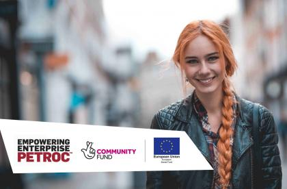Young woman with long red hair smiling at camera. Logos for Empowering Enterprise, National Lottery Community Fund and European Social Fund